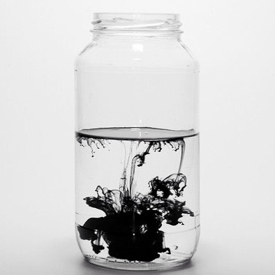 black ink spreading in glass of water